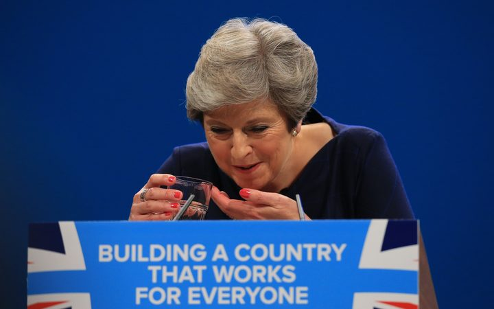 Theresa May splutters as she drinks water while losing her voice during her keynote speech.
