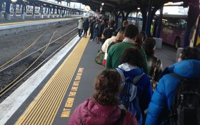 People queue for buses at the train station in Wellington.