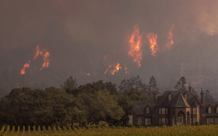 Flames rise behind Ledson Winery on 14 October 2017 in Kenwood, near Santa Rosa, California.