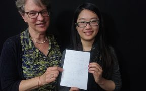 Eva Radich with Chunxaio Lu showing off her Chinese language notes.
