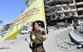 Rojda Felat, a Syrian Democratic Forces (SDF) commander, waves her group's flag at the iconic Al-Naim square in Raqqa.