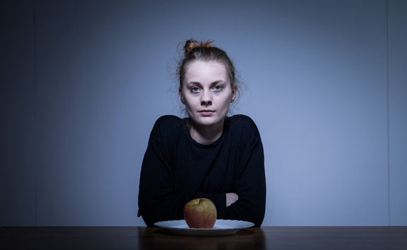 A photo of a girl eating only an apple for dinner