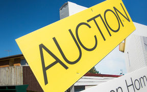 An auction sign outside a house for sale in Auckland.