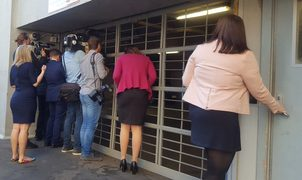 Political reporters peeking for clues through a garage door in the Beehive.