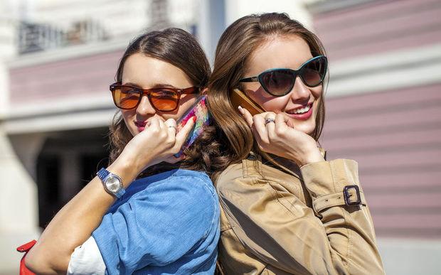 Two women talking on phones