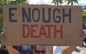 A Manus Island detainee holds a placard during the 81st day of protest.