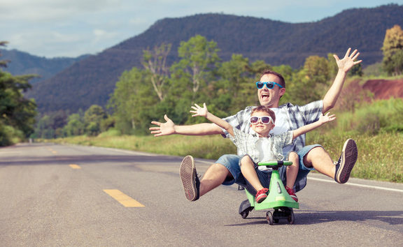 A photo of a father and son riding on a  skateboard playing on the road at the day time.