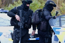 Armed police officers leave an address in Ohakune during the search.