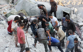 Residents and members of the Syrian Civil Defence, also known as White Helmets, search for victims amid the rubble of a building following a reported air strike in the northwestern town of Harim in Idlib province, on 29 September 2017.