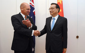 China's Premier Li Keqiang shakes hands the President of the Senate Stephen Parry (L) at Government House in Canberra on March 23, 2017.
