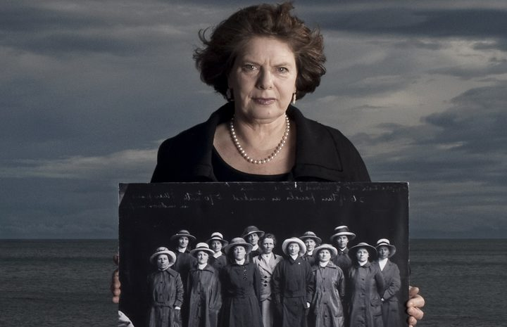Jane Tolerton holding a photo of the NZ Volunteer Sisterhood before the first group left Wellington for Egypt in October 1915. Hatless in the middle is Ettie Rout, the one woman associated with NZ in WWI whose name is well known.