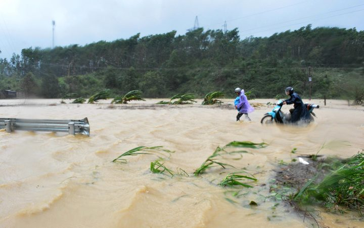 Walking through floodwaters on a highway in the central province of Dak Lak brought by Typhoon Damrey.