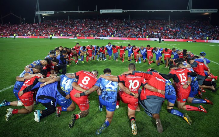 Tongan and Samoan players embrace in prayer