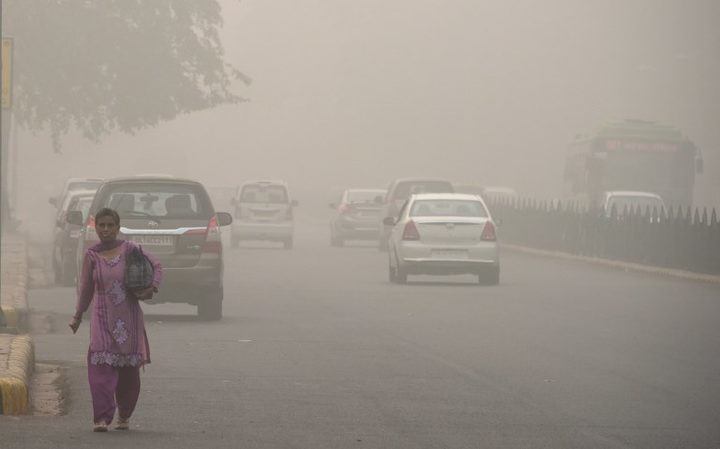 An Indian woman walks on a road during heavy smog conditions in New Delhi.