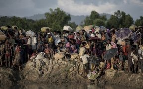 Rohingya refugees wait after crossing the Naf river from Myanmar into Bangladesh in Whaikhyang on October 9.