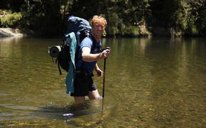 Geoff Chapple crossing a river on Te Araroa - New Zealand's Trail.