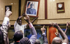 A portrait of Robert Mugabe is removed from the International Conference centre, where parliament had been sitting.