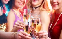 Women clink glasses of champagne at a party