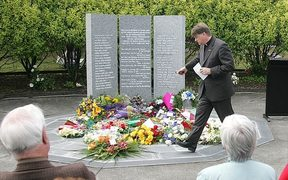 Rev. Dr Richard Waugh, during the Mt. Erebus 25th anniversary service at Auckland's Waikumete Cemetery. He is sprinkling water, brought from Mt Erebus, over flowers in front of the memorial to 44 victims, November 2004.  (Air New Zealand)