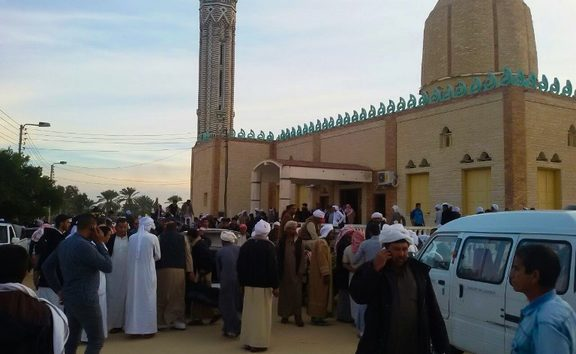 People gather at the site of the Egypt Sinai mosque bombing in Al-Arish, Egypt.