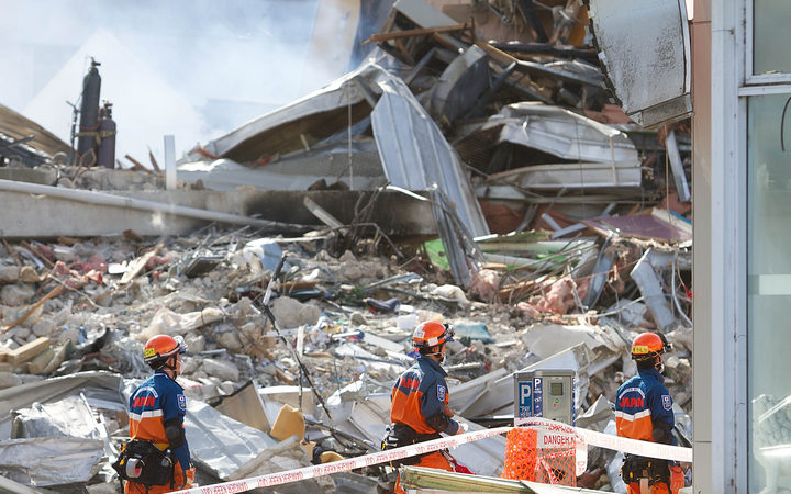 Japanese rescuers walk past the smoking ruins of the CTV building.