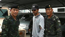 Thai police escort a suspect (centre) arrested on the Thai side of the Cambodian border on 1 September in connection with the bomb attack in Bangkok on 17 August.