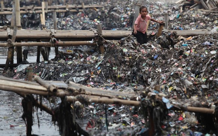 An Indonesian child collects rubbish on the coast near a fishing village in Jakarta, Indonesia.