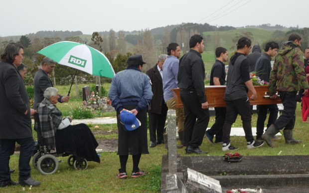 Mourners carry the coffin to the graveside.