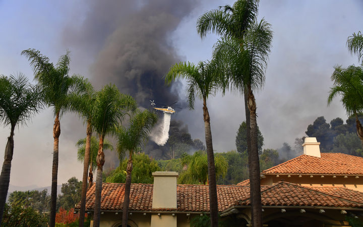 A helicopter drops water on fires threatening homes in Bel Air.