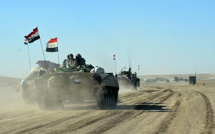 Members of the Iraqi forces and the Hashed al-Shaabi (Popular Mobilisation units) ride on infanty-fighting vehicles near the Iraqi-Syrian border
