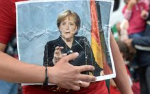 A refugee holds a picture of German Chancellor Angela Merkel after the arrival of refugees at the main train station in Munich, southern Germany, September 05, 2015.