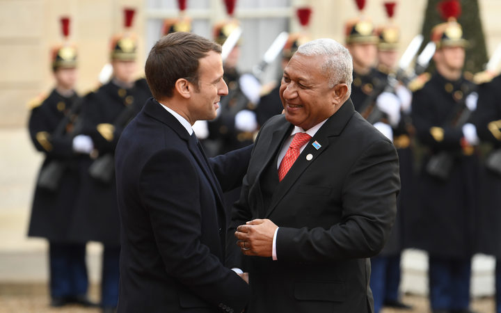 French President Emmanuel Macron (L) greets Prime Minister of Fiji Frank Bainimarama as he arrives at the the One Planet Summit.