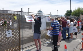 Families of those who died tie their placards to the fence surrounding the CTV site.