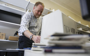 Mick Crouch works with an old-technology floppy disk reader as he preserves New Zealand's archives