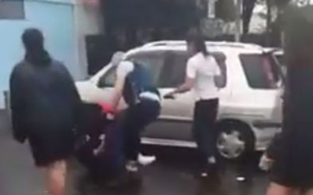A screenshot from the video, showing policemen trying to intervene.