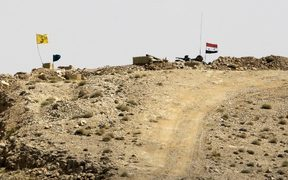 A picture taken in August during a tour guided by the Lebanese Shiite Hezbollah movement shows the flags of the movement and the Syrian government (R) flying over a position held by the Syrian government forces near the border with Lebanon.