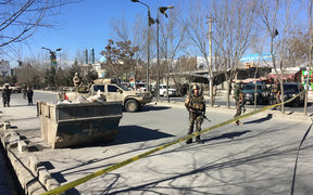 Afghan security forces stand guard near the site of multiple blasts in Kabul on December 28.