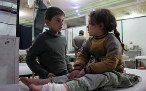 A Syrian boy talks to an injured girl as she lies on an operating bed in an emergency room in the rebel-held town of Douma in Syria's eastern Ghouta region on December 17.
