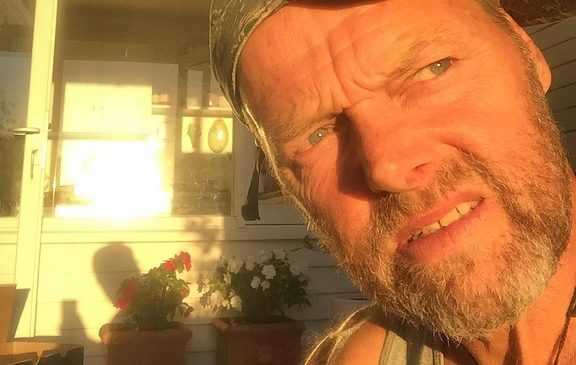 A portrait of Bruce Hopkins at home in Auckland, staring into the sun and wondering when he will get back on the trail.