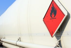 A fuel and flammable liquid tanker truck with a fire hazard warning sticker.