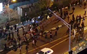 Men pull at a fence in a street in Tehran on Saturday, in a video released by Iran's Mehr News agency.