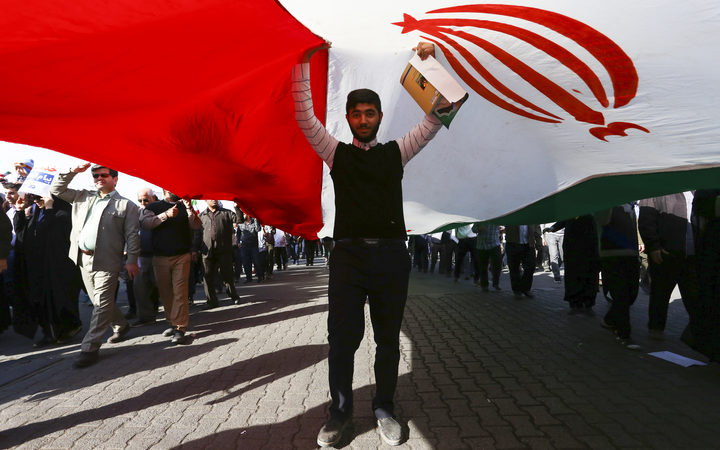 A pro-government demonstrator stands under an Iranian flag during a march in Iran's southwestern city of Ahvaz on January 3, 2018.