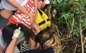 Medical staff stablise the girl after she accidentally impaled her leg on a tree branch.