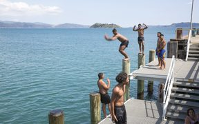 A group of teenagers and kids cooling off at Petone Wharf.