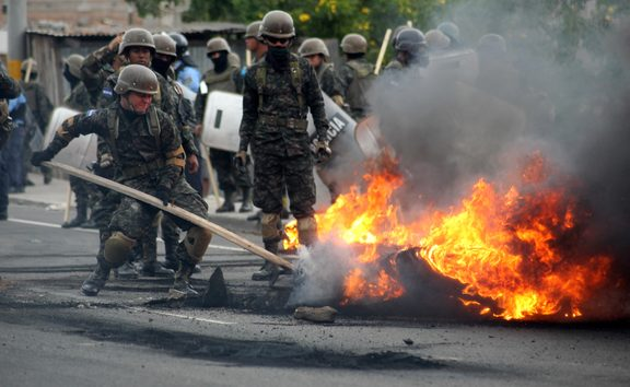 Riot police and soldiers try to remove burnt tires after clashes with supporters of the Honduran Opposition Alliance Against the Dictatorship in Tegucigalpa on Saturday.