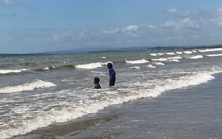 Children brave the water on Milford Beach, where a public heath warning is in effect.