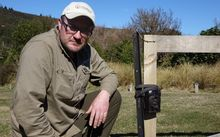 Orokonui's conservation manager, Elton Smith, with one of the motion cameras used to spot the stoat.