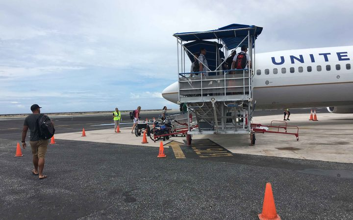 Passengers board a United Airlines flight in Majuro. For the first time in late January, Marshall Islands Immigration officials detained several passengers at Majuro's international airport for questioning in relation to participation in illegal adoptions in the United States.