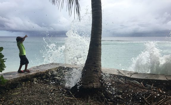In this photo from last month's peak high tide in Majuro, a local youngster reacts as king tide-driven waves wash over a seawall on Majuro. Significantly higher tides are anticipated this week.