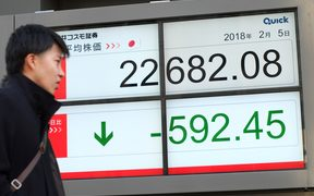 A pedestrian walks past an electronics stock indicator showing the closing numbers on the Tokyo Stock Exchange in Tokyo on February 5, 2018.